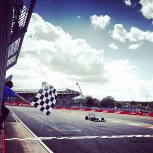 Lewis Hamilton takes the checkered flag at his home race. Photo from Lewis Hamilton's Facebook page.