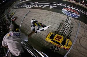 Joey Logano takes the checkered in Bristol's night race. Photo by Brian Lawdermilk/NASCAR via Getty Images.