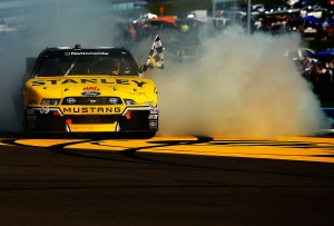 Marcos Ambrose does a celebratory burnout after his win on Saturday. Photo by Jared Wickerham/Getty Images.